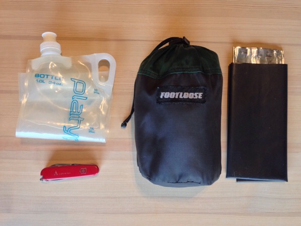 Backpacking cook set packed with Platypus water bottle, Victorinox Camper Swiss Army Knife and homemade wind break and mat