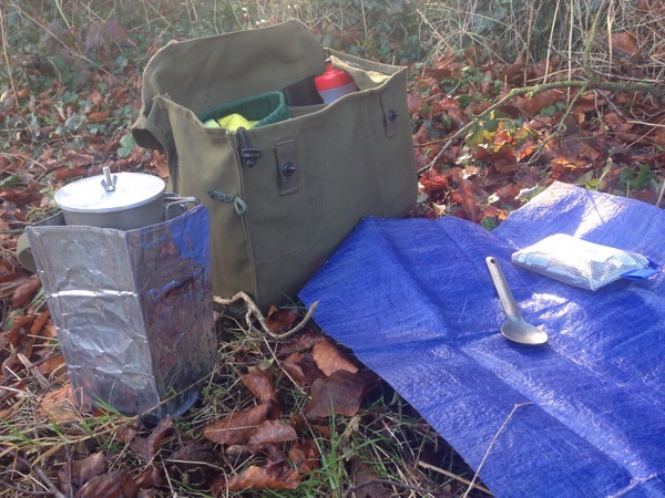 A stop for a brew - Finnish gas mask bag, Alpkit Kraku gas stove (behind a wind shield) and a Sea to Summit alloy spoon